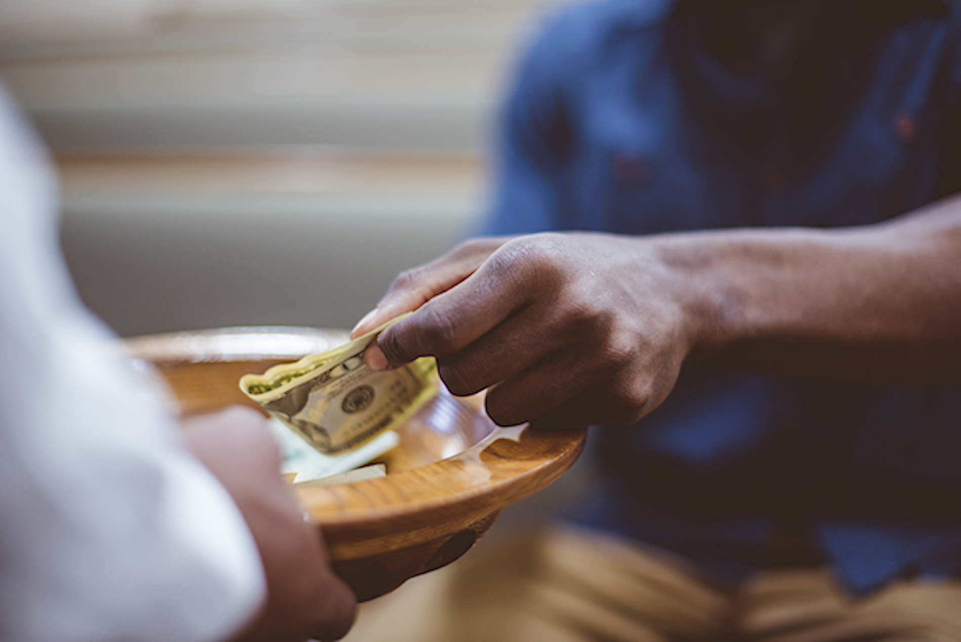 Man placing cash in a wooden donation plate